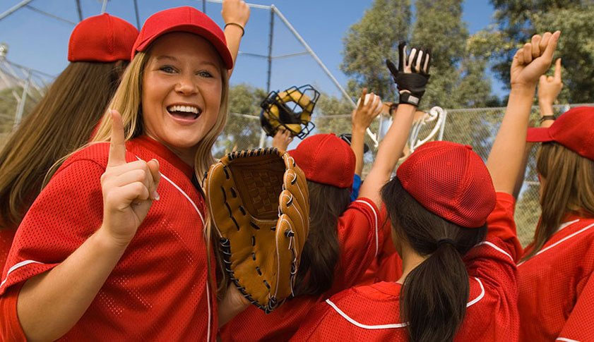 A smiling woman dressed in a red shirt and red hat gesturing number 1 with her hand is among a baseball team of young girls.