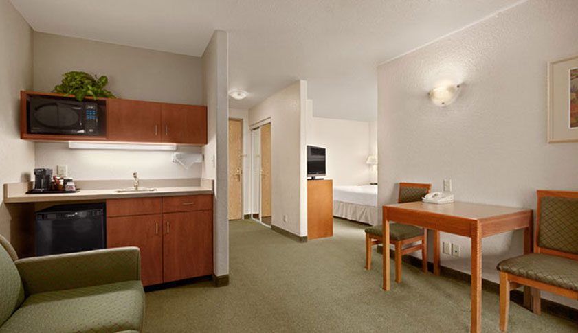 The Extended Stay room at Days Inn Red Deer has green carpeting and is furnished with a green couch, eating table and chairs and fully equipped kitchenette.