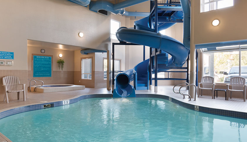 Indoor pool and hot tub with a slide  Hotels with Waterslides – Amenities – Days Inn Red Deer