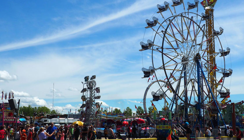 A ferris stands amidst the Westerner Fair Expo in Red Deer, Alberta on a bright sunny day.