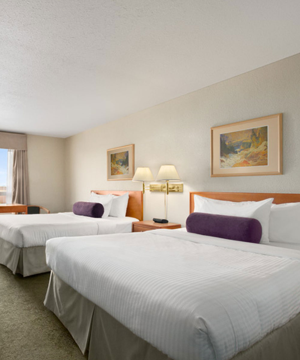 Two bed suite with bedside table, lamps and two beds in white, purple and beige color bed linen at Days Inn Red Deer, Alberta.