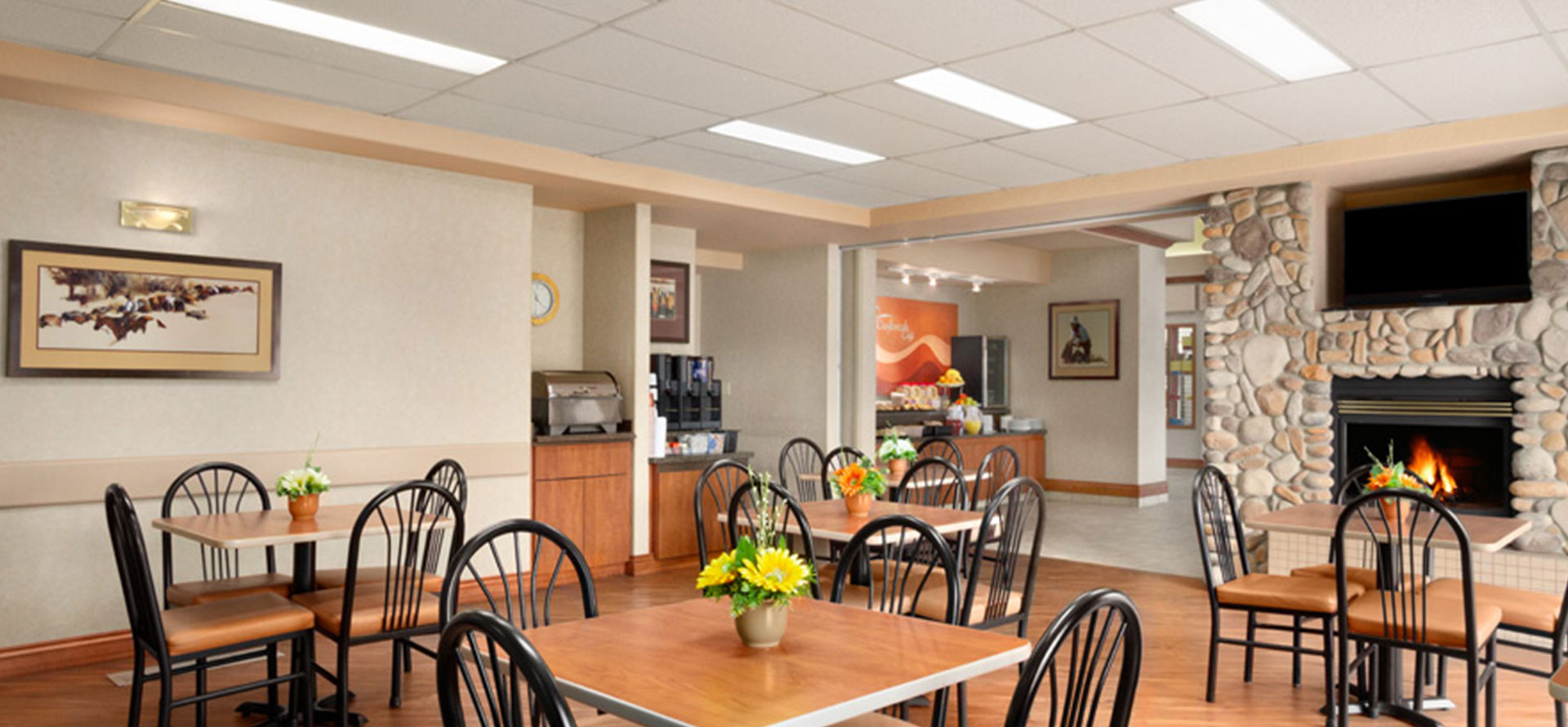 Large view of a bright breakfast room with stone fireplace, tables, chairs and fresh flowers at Days Inn Red Deer, Alberta.