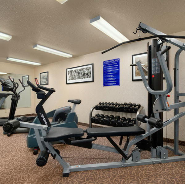 A brightly lit workout room at Days Inn Red Deer, Alberta with several pieces of exercise equipment and weights