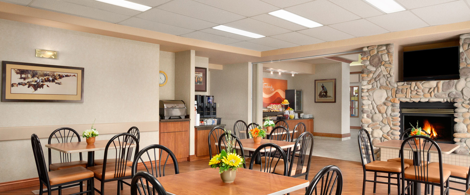 Large panoramic view of the brightly lit breakfast room at Days Inn, Red Deer featuring clean eating tables with comfortable chairs and stone fireplace.