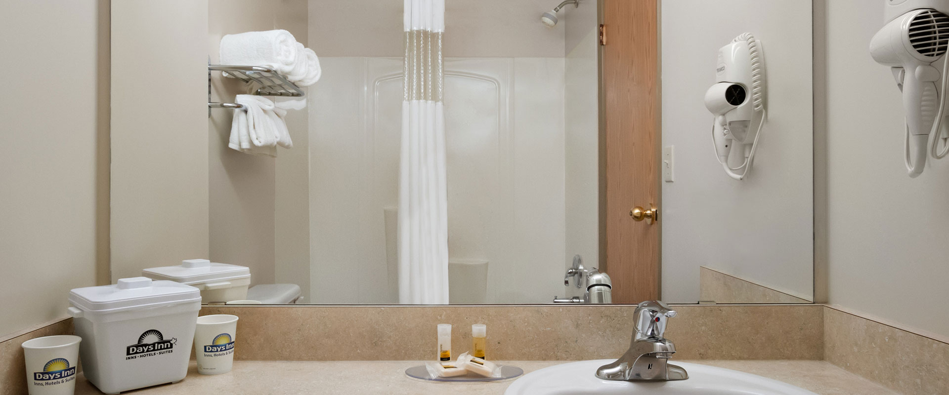 Large view of a guest bathroom at Days Inn Red Deer, Alberta with large mirror over the sink and a shower and shower curtain.