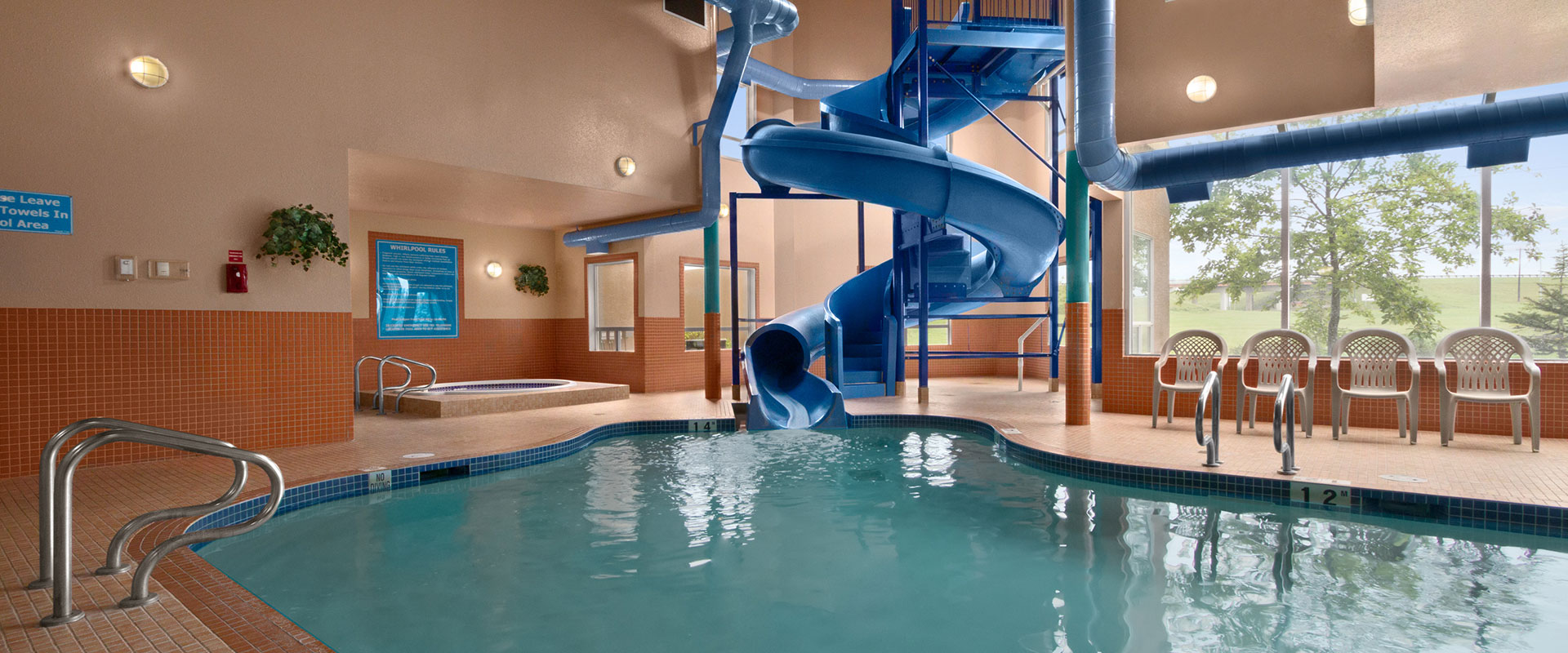 Heated indoor pool with a large waterslide and hot tub at Days Inn Red Deer, Alberta.