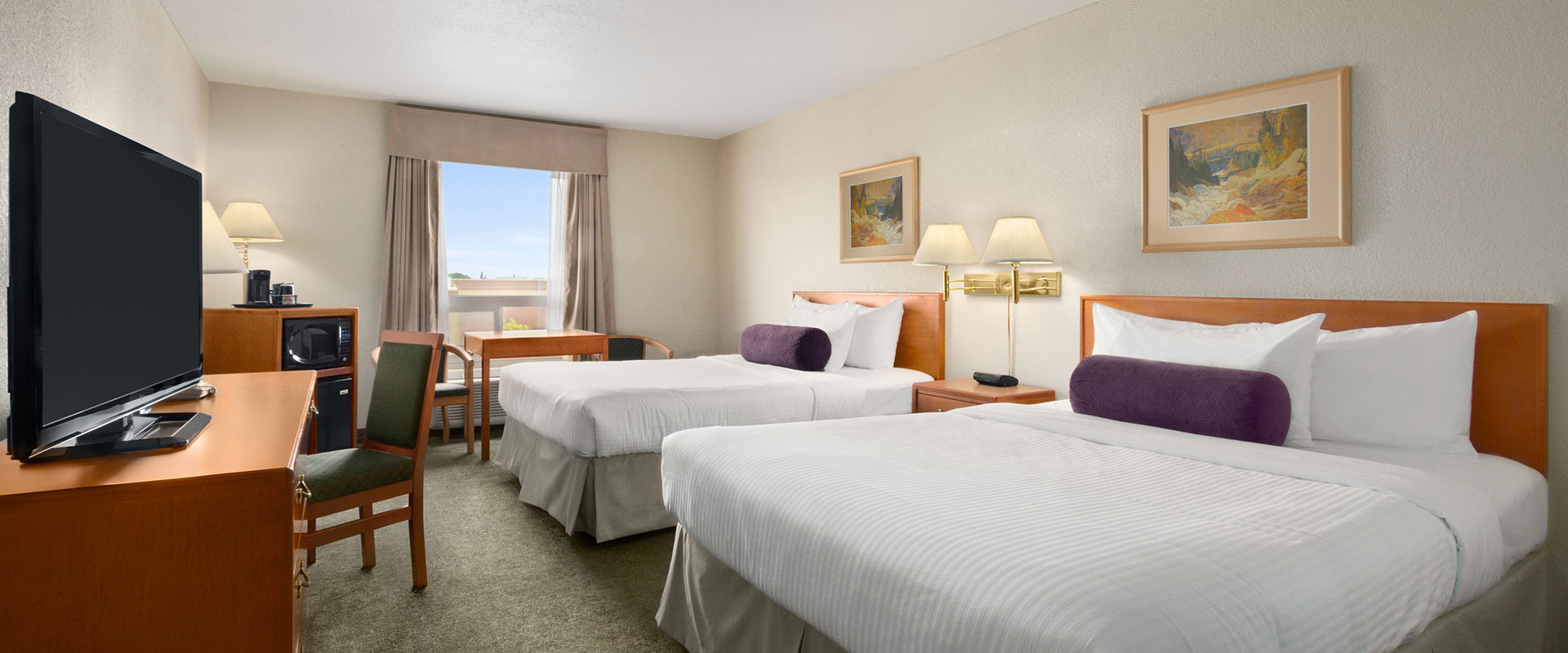 Two bed business class suite with microwave, TV, work table, lamps and chairs at Days Inn Red Deer, Alberta.