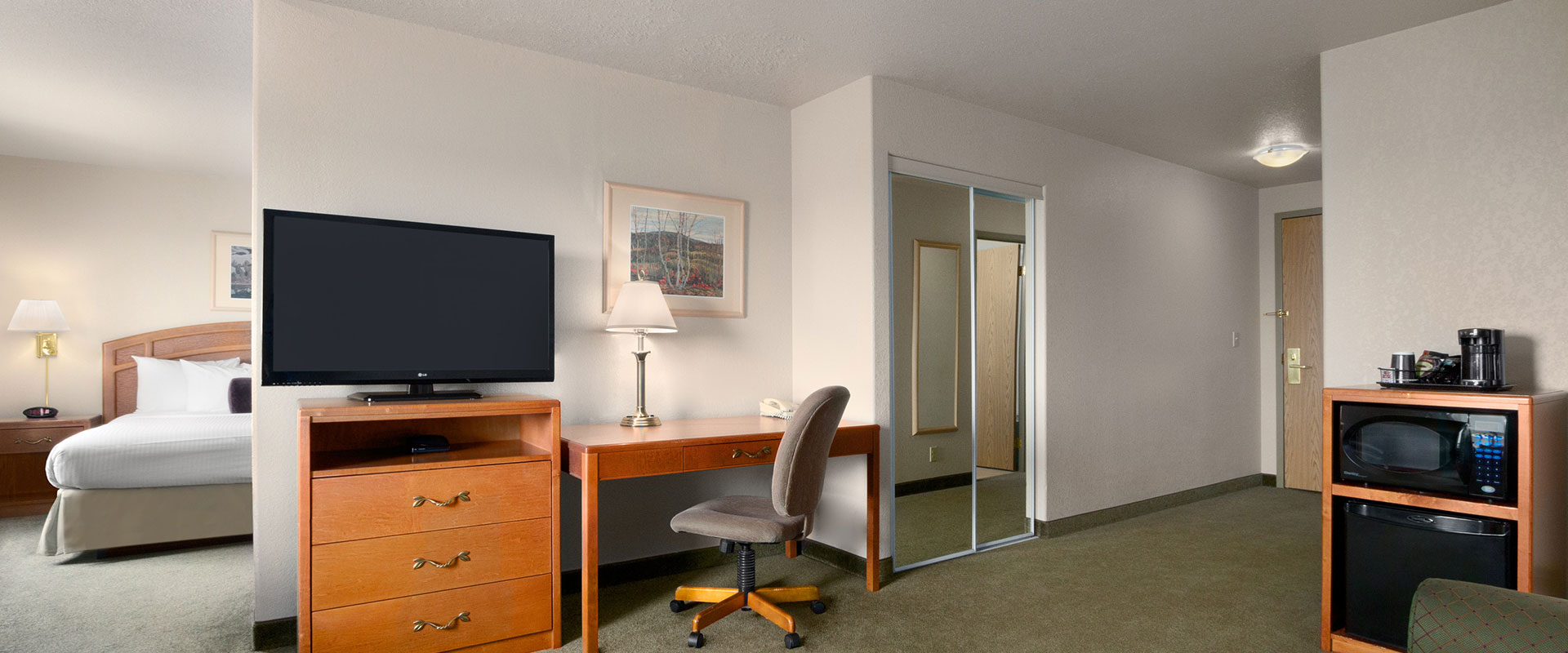 Large view of a suite at Days Inn Red Deer, Alberta with a rectangular work table and chair, a TV perched on a cabinet of drawers and mirrored closet.