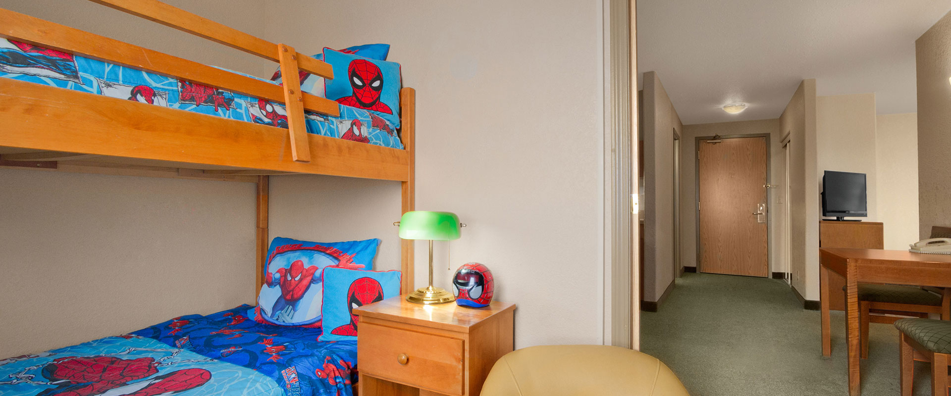 Large sized view of a kid friendly suite featuring bunk beds with Spiderman bed linen and pillows at Days Inn Red Deer, Alberta.