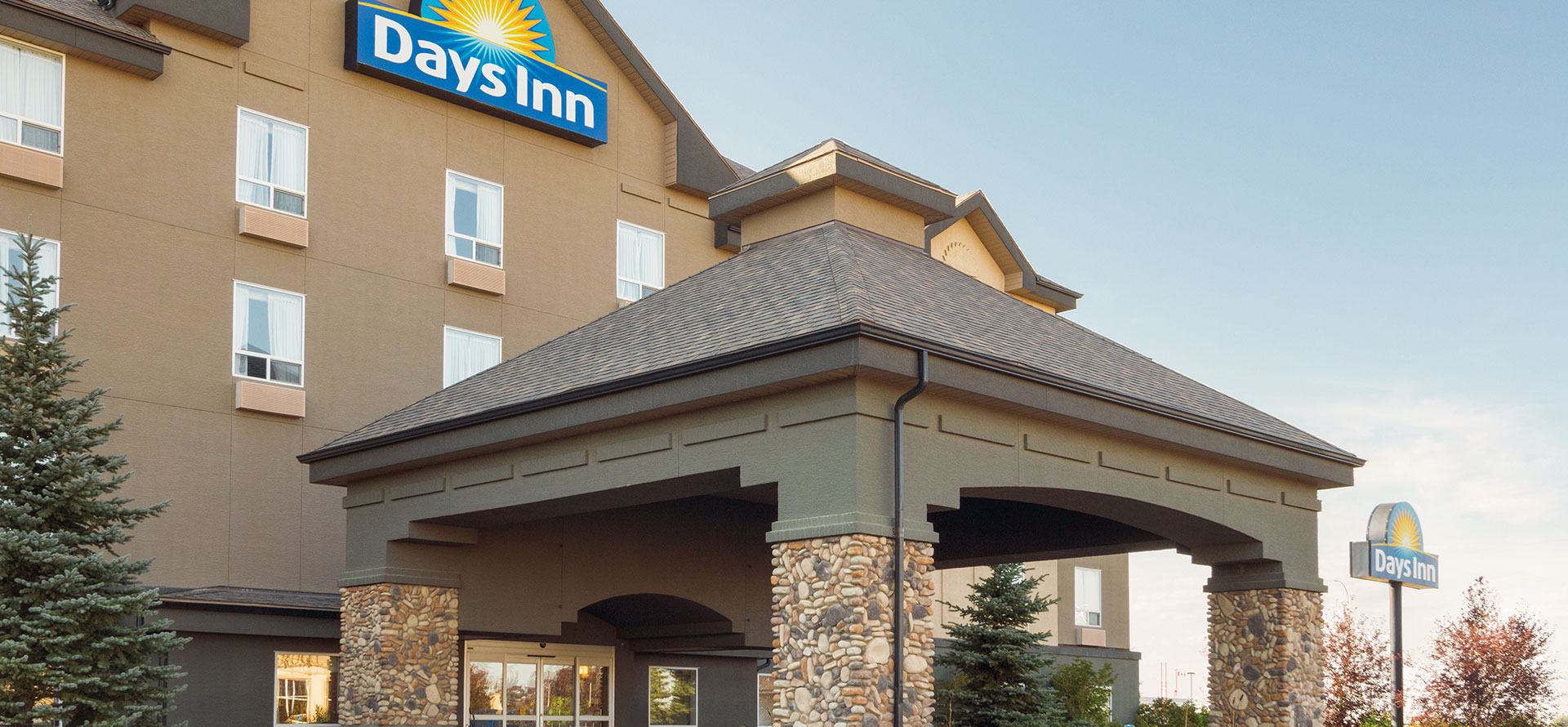 Large view of the portico covered entranceway, flanked by pine trees to Days Inn Red Deer, Alberta.