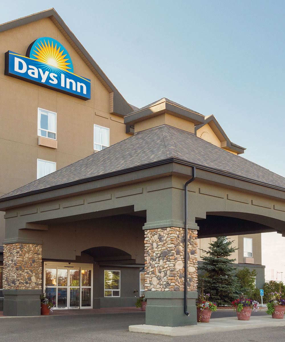 Entranceway to Days Inn Red Deer, Alberta featuring a large stone and concrete portico, green trees and larged pots of flowers placed throughout.