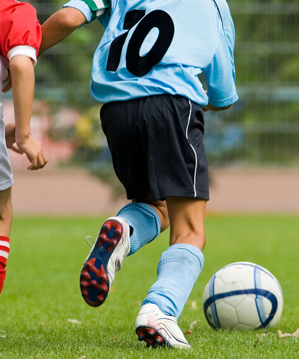A boy dressed in a number 10 blue shirt, blue socks and black shorts playing soccer.