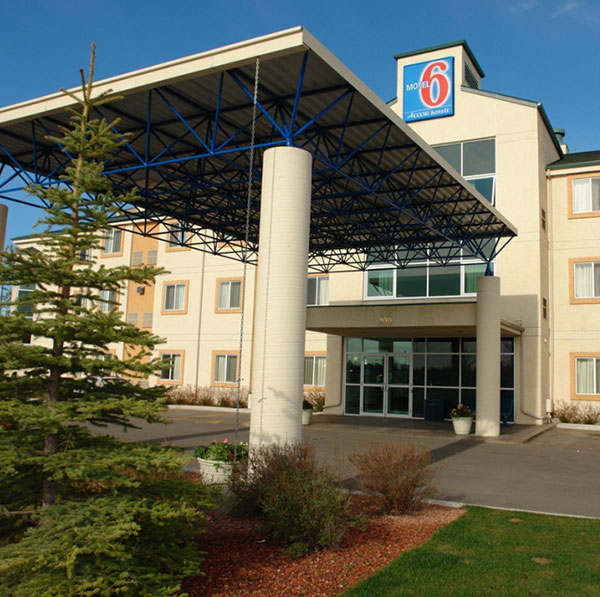The entrance view of Motel 6 Red Deer with a large portico and four flanking columns and a green tree.