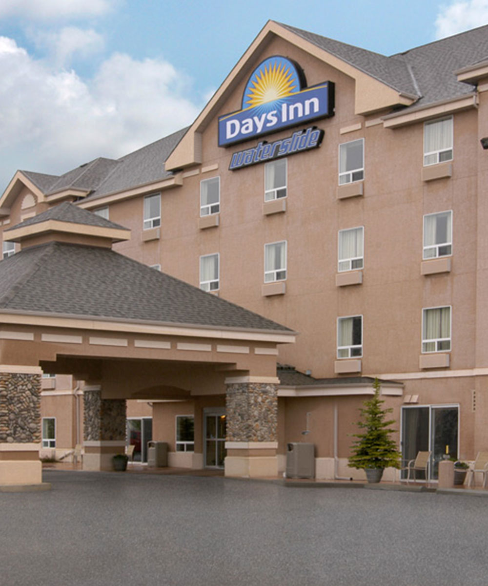 Part view of the main entrance to Days Inn Red Deer, Alberta featuring a large stone and concrete portico and the corporate at the the top of the hotel.