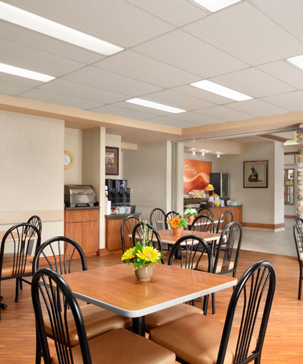 Chairs and tables are placed by the coffee and tea service nook at the Daybreak Café in Days Inn Red Deer.