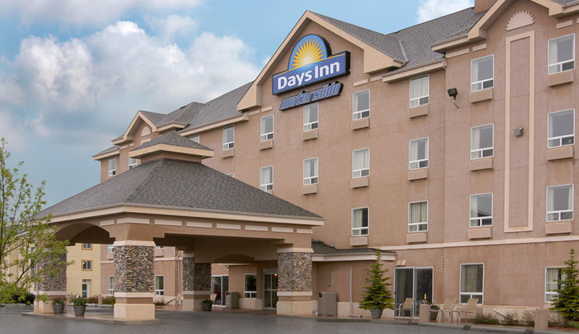 A large architectural concrete and stone portico covers the entrance to Days Inn Red Deer with the corporate logo and waterslide sign perched at the top of the hotel.