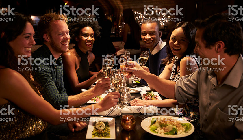 A group of young male and female friends are eating out and toasting with a glass of champagne.