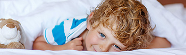 Small photo of a smiling boy with blonde hair and blue eyes peering out from under white bed covers.