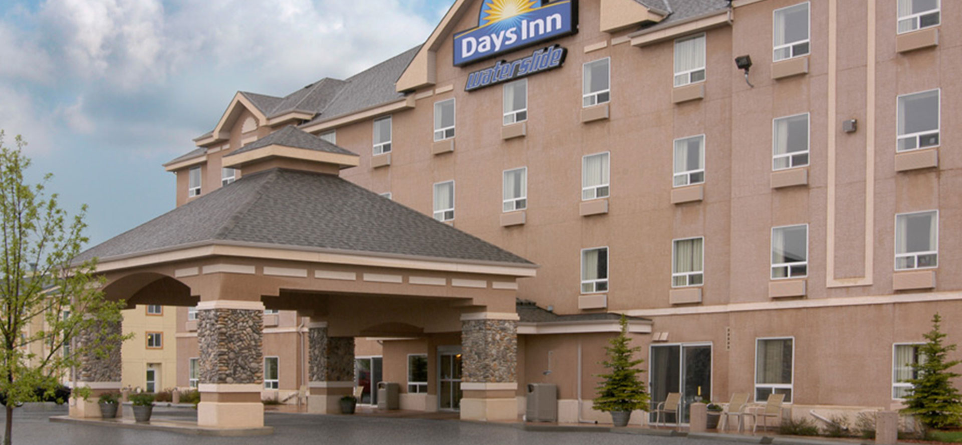 Large view of main entrance to Days Inn Red Deer, Alberta with a stone and concrete portico and the corporate logo placed at the summit of the hotel.