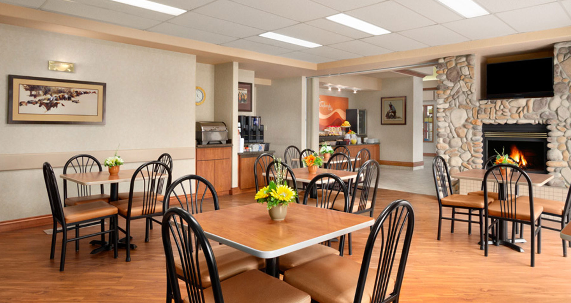Large panoramic view of the Daybreak Café at Days Inn Red Deer with square eating tables and comfortable chairs are placed around a lit fireplace.