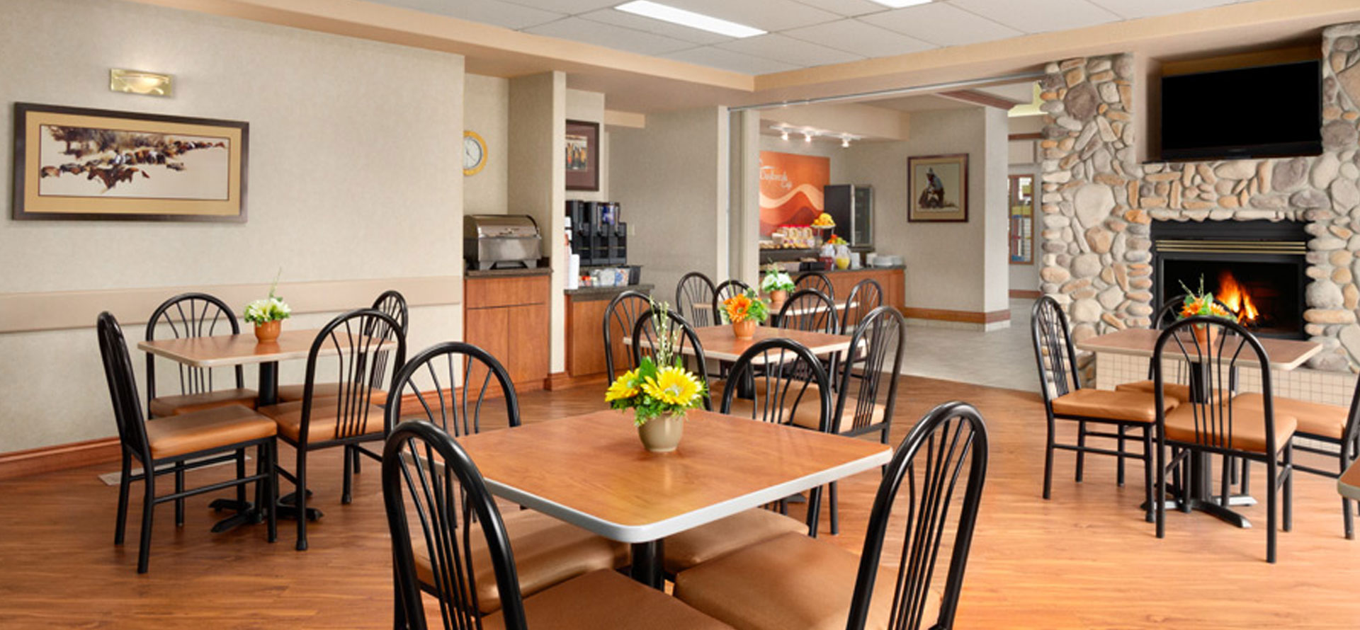 Large view of the sunny breakfast room at Days Inn Red Deer, Alberta with tables and bright fresh flowers and roaring fireplace.