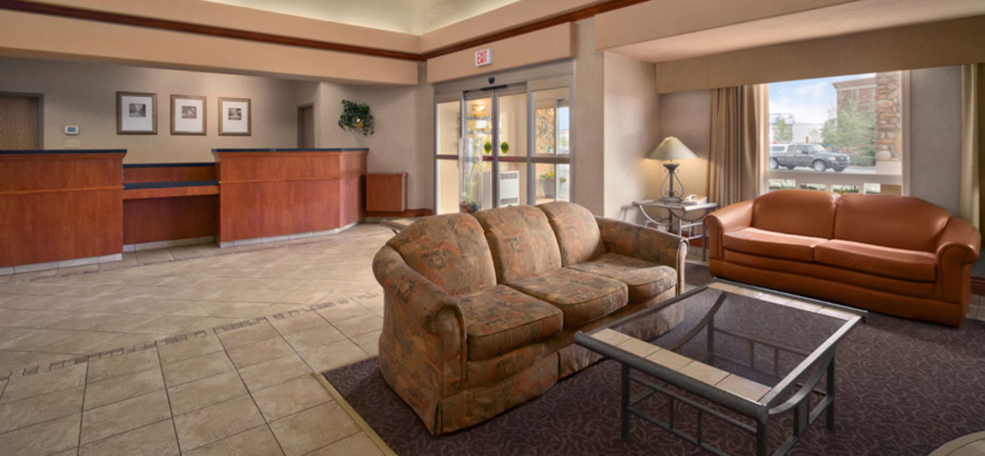 A beige fabric covered sofa, a brown leather couch and a square metal and glass coffee table sits on an area rug in the lobby of Days Inn Red Deer.