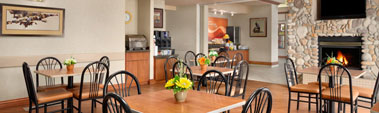 Small view of the Daybreak Café at Days Inn Red Deer, Alberta with eating tables, chairs and a stone fireplace.
