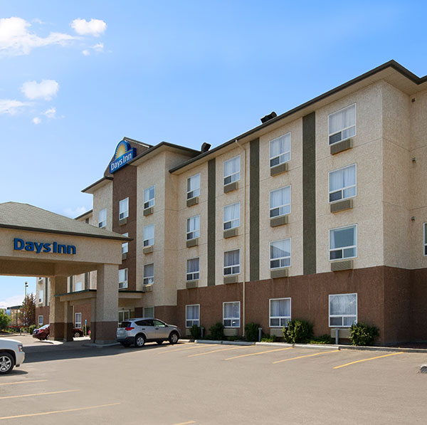 Parking lot view of Days Inn Red Deer, Alberta with a concrete portico covered entrance.
