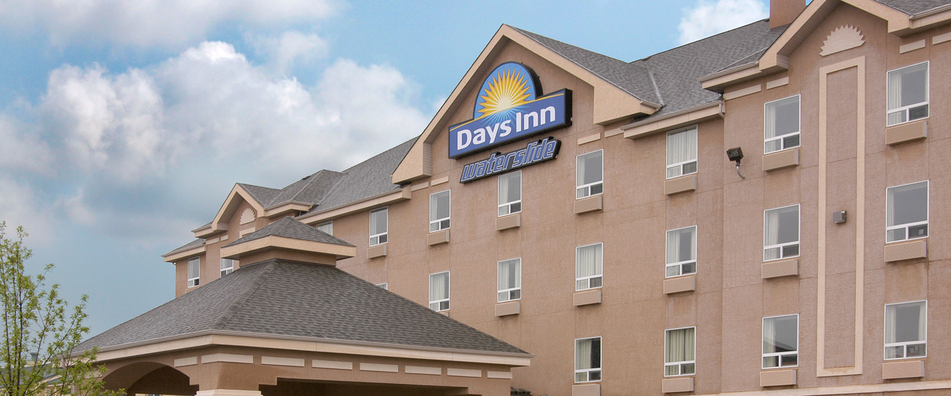 Large sized view of the exterior building of Days Inn Red Deer, Alberta with the company logo signage and a smaller sign that reads waterslide.