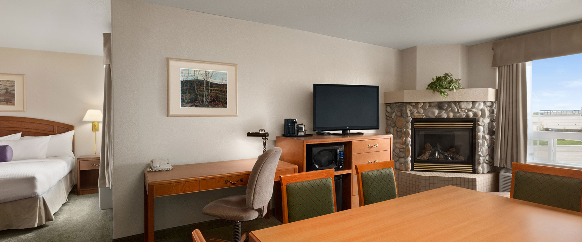 Large view of a one bed suite with workspace, office chair, TV, microwave and stone fireplace at Days Inn Red Deer, Alberta.