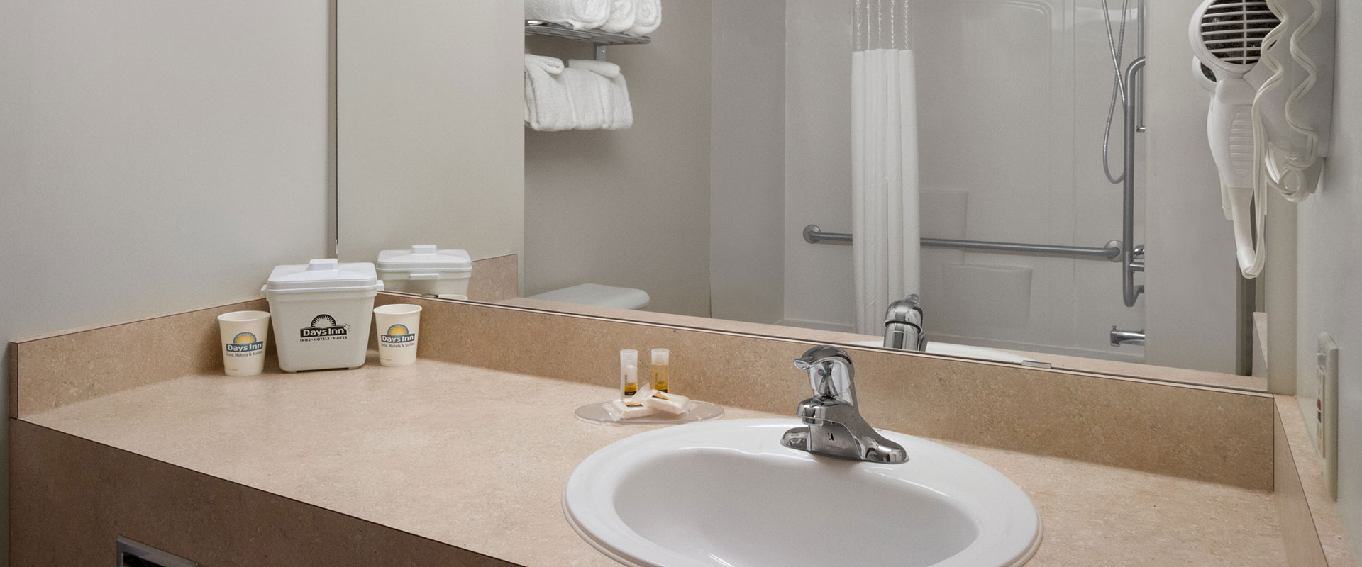 A typical bathroom suite at Days Inn Red Deer, Alberta features stocked linen, hair dryer, complimentary soap and paper cups with company logo.