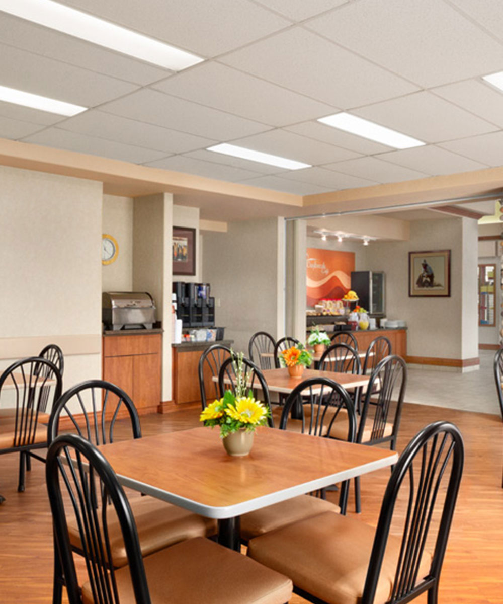 The breakfast room at Days Inn Red Deer, Alberta with coffee kiosk, breakfast counter and eating table with chairs and flowers.