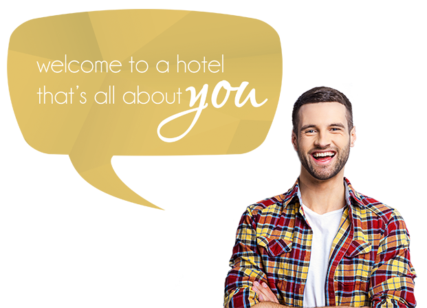 Smiling bearded man in a multi colored plaid shirt speaking through a speech bubble  Welcome to a hotel that's all about you.